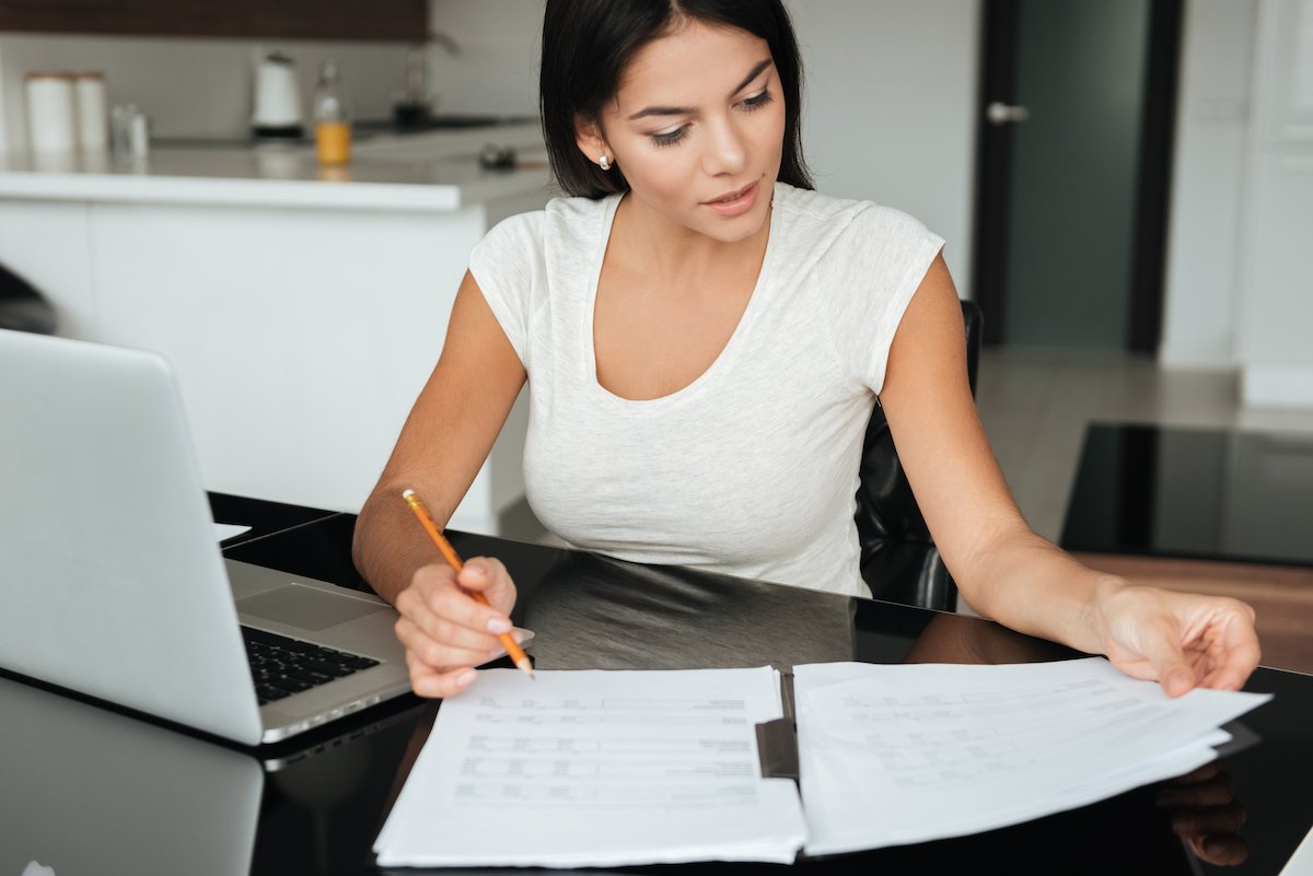 Concentrated woman analyzing home finances while looking at documents
