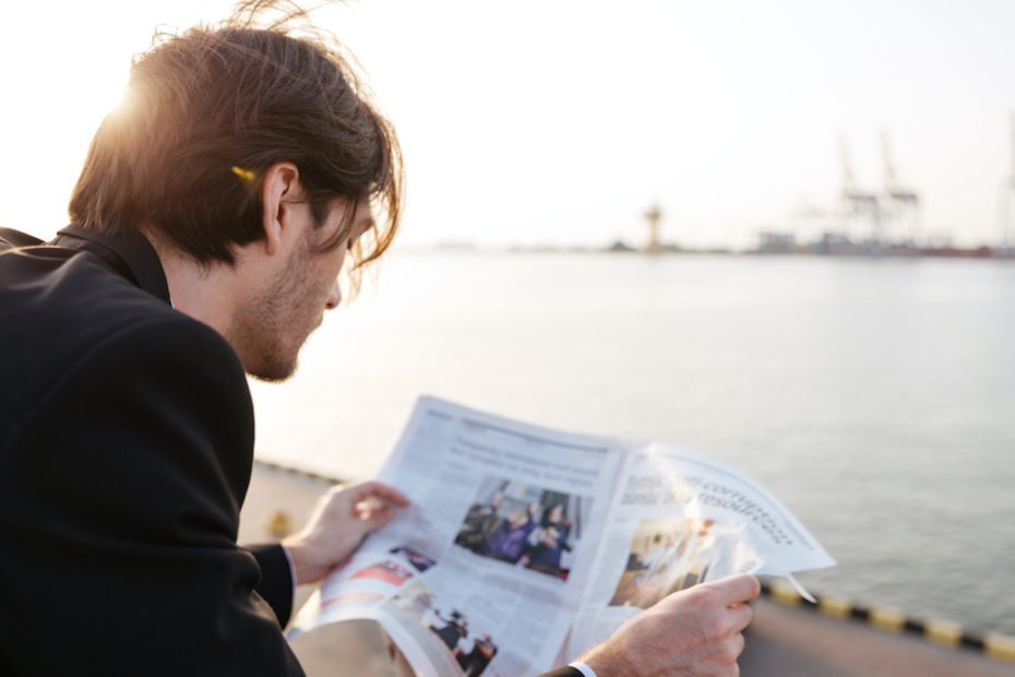 Successful businessman reading newspaper